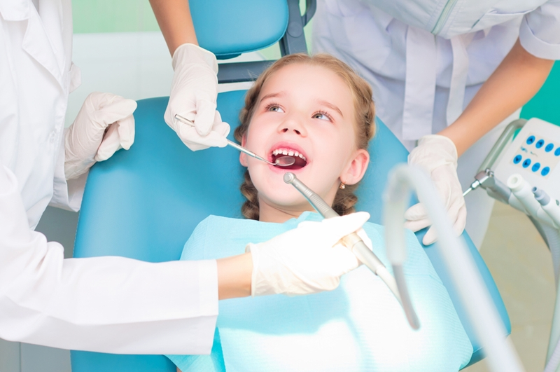 Pediatric dentist and hygienist cleaning child's mouth.